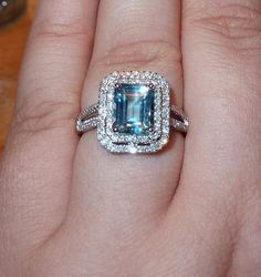 3 carat emerald cut aquamarine in a double halo with pave diamonds and a split shank setting