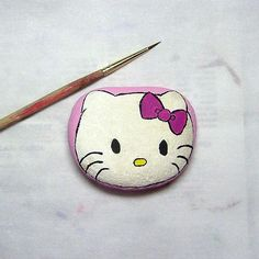 Hello Kitty painted on a rock and like OMG! get some yourself some pawtastic adorable cat shirts, cat socks, and other cat apparel by tapping the pin!