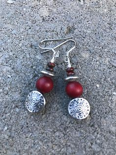 This beautiful pair of boho style earrings are made with silver tibetian style beads, red wood beads, and red Czech glass beads. Boho earrings hang 2 inches from silver plated earwire.