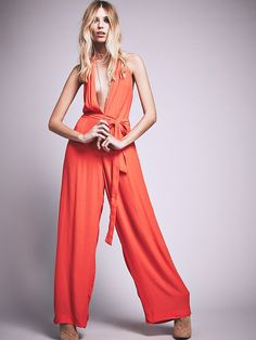 Sammie Jumpsuit | Make a lasting impression in this daring jumpsuit, featuring plunging neckline and open back. Belted waist tie and wide legged silhouette for an effortless look. Adjustable halter-style ties for a flattering fit.