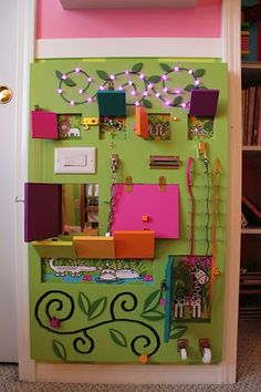 Homemade Busy Board / Activity Board: Great for developing toddlers' small motor skills. 10 doors to open, ten different latches, jungle animals under the doors plus a mirror, lights that work, a door latch, lacing strings, a pulley, castor wheels, and a flower track.