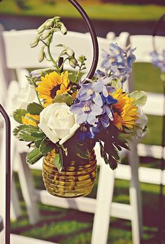 A rrangements of sunflowers, delphiniums, and roses which hung from shepherd's hooks. Alea Moore Photography.