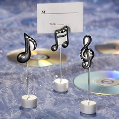 Your guests are sure to be singing the praises of these unique musical note place card holders.There will be music in the air as your guests find their seating assignments whimsically displayed in these cute musical note place card holders. Perfect for any number of event themes, the resin and wire place card holders come in three assorted musical note designs and feature a round silver base with a wire extension with a black and silver rhinestone-embellished note at the top.  Sold with…
