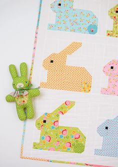 "Hippity Hoppity is a cot size Easter Bunny Quilt. The 10"" x 10"" are perfect for smaller Easter projects like table runners, place mats and pillows! Easy quilt pattern, Easter quilt ideas, Easter crafts, Easter DIY project, bunny quilt block, pillow, cushion, baby quilt, sewing for baby. Patchwork Anleitung, Nähanleitung Patchworkdecke, Kissen, Hase, Häschen, Oster Ideen, Patchwork Ideen, Oster Geschenke selber machen, Nähen für Ostern, Ostern DIY, Nähen fürs Baby. Nadra Ridgeway, ellis…"
