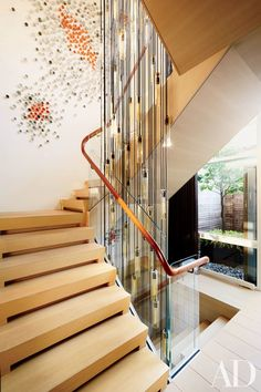 The couple called on architectural designer Thomas Juul-Hansen and decorator Amy Lau to combine five apartments into a stunning triplex. Juul-Hansen opened up the stairwell, adding white-oak steps with recessed lighting and a glass balustrade topped by a hand-carved rosewood rail   archdigest.com