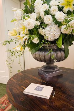 Hydrangeas, roses, flowering vines and yellow and white lilies are beautifullyarranged in a stone urn.