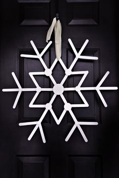 For those who love glitter! Check out this super cute and super easy holiday craft for the front door. This giant glitter-covered snowflake — made with wooden craft sticks, glue and some paint