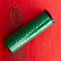 A stainless steel coffee tumbler with a hammered texture and cool green finish.