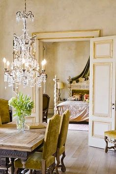 Rustic farm table with elegant antique velvet covered chairs, beautiful french doors and plastered walls add charm