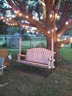 Backyard swing with lights in the trees.
