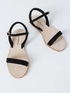 Simple and low profile sandals with black suede tubular straps across the toes and at the heel. These sandals fasten across the front of the ankles with a suede strap and buckle. - Slight wedge heel m