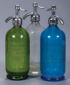 """Three Miles City, Montana Seltzer Bottles. All full size (11 1/2"""" tall) Etched glass bottles. a) Green, """"W H Bullard - Miles City Mont."""" with Miles City Bottling Works cap.  b) Blue, """"M W Milligan - Miles City Mont."""" with Coca Cola Bott Co. cap.  c) Clear, Louis Bach - Miles City Mont"""" in horseshoe with Miles City Bottling Works cap.  All 11 1/2"""" overall.  Provenance: From the Estate of Thomas W. Lorimer. Etched Glass, Glass Etching, Miles City, Western Saloon, Soap Dispenser, Glass Bottles, Coca Cola, Montana, Cap"""