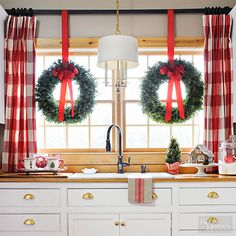 When you're crunched for time, stick to a classic design concept: symmetry. Hang two matching purchased wreaths from your windows with bright red ribbon, suspending them from the curtain rod.