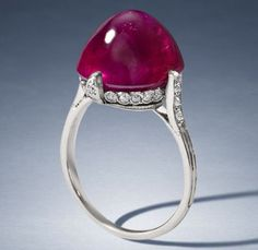 Van Cleef & Arpels - A ruby single-stone ring (1923) - The sugarloaf cabochon ruby, displaying asterism, weighing 13.34 carats, within a delicate single-cut diamond mount, with beaded and millegrain detail, mounted in platinum, signed Van Cleef Arpels, numbered 21844, French assay mark, ring size K½.