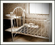 Vintage Crib - Wandering through the ghost town of Bodie, California, I was fascinated by the vintage furnishings inside some of the buildings. I love this iron crib.  Original photograph by Marcia Socolik, available as a print on paper, canvas, metal, or acrylic, or as a greeting card. If framed - you select frame and mat. . All Rights Reserved © 2013 Alan & Marcia Socolik. #Photography #WallArt #Decor #Vintage