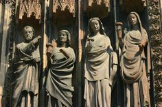 Wise virgins holding their lamps upright at left door of Cathedral. Strasbourg, France.