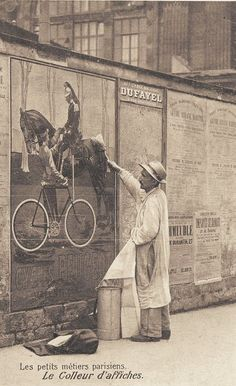 Gluing posters to a wall, somewhere in France, 1900.