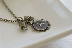 This lovely necklace features an embossed uppercasetypewriterinitial letterbrass charm, embellished with a filigree jewelry component, dangling from a butterfly bow charm. Cable chain closes with a lobster clasp.   - The chain length is approximately 18 inches (45 cm).   - Initial charm with filigree component measures 16 mm (5/8 inch) in diameter and is available in all 26 alphabetic letters.   - Pendant measures approximately 1.25 inches (3,00 cm) in height.   ***MADE TO ORDER***   - J...