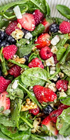 This healthy Strawberry Spinach Salad Recipe is packed with strawberries, raspberries, and blueberries with walnuts and feta on a bed of spinach and homemade dressing! #valentinascorner #salad #strawberrysalad #spinach #spinachsalad #strawberry #sidedish #strawberry