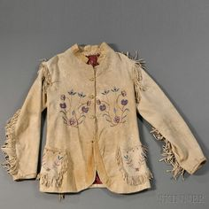 """Plateau Embroidered Buckskin Jacket, c. late 19th century, cloth-lined and with fringed seams, the pockets and front with floral designs done in multicolored threads, with three remaining gold-plated figurative commercial buttons, old tag reads """"Coat of Buckskin made by Cour'd A Line Squaw"""""""