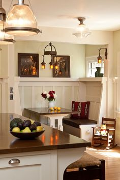 """Kitchens were treated to light colors and """"sanitary"""" white paint. This revival kitchen brightens the cream-color paint with a tint of sage green on walls and in wainscot panels. It's just enough color to bridge the difference between white paint and the warm floor and mica fixtures."""