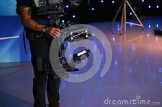 Photo about Man using a steadicam in a television studio - specific equipment to stabilize the camcorder. Image of modern, media, film - 79215205 Camcorder, Editorial, Technology, Studio, Film, Fictional Characters, Image, Video Camera, Tech
