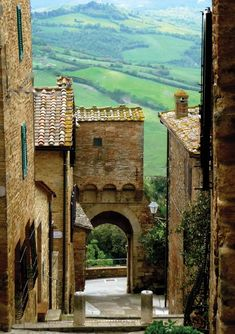 View through the oldest doorway of the Radicondoli, the Porta Olla, into the verdant green May valley beyond in Tuscany, Italy