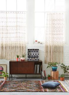 The fringed curtains, done in a style reminiscent of crochet or macrame, are beautiful. The records, many plants, and natural tones of the decor are soothing to the eye.