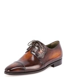 Berluti leather derby shoe. Lace-up front. Cap toe with perforated brogue details. Stacked flat heel. Leather lining and soles. Made in Italy.