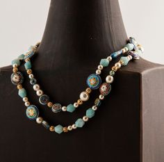 Long, eye-catching and elegant vintage-style necklace. Made with Amazonite gemstone nuggets, handmade Cloisonne beads, filigree gold-plated beads and glass pearls. Can be worn as a long single strand or a shorter two-strand necklace. Sold.