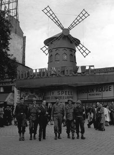 World War Two, Paris, France, 12th September 1944, U,S, Officers are taken on a guided tour around the disrict of Montmatre, after the liberation of France, Behind the group is the famous entertainment venue, The Moulin Rouge (Photo by Popperfoto/Getty Images)