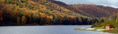 A boat rental is by a lake surrounded by mountains blanketed by red- orange- and green-leaved trees at Lyman Run State Park, Pennsylvania.  hiking, ATV trail, geocaching, picnic, pavilion, swimming beach, boating, boat rentals, lake fishing, stream fishing, hunting, programs, snowmobiling, ice fishing, ice skating, camping