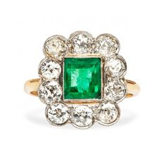 Montrose is a Victorian era flower ring featuring a 1.20ct Rectangular Step Cut emerald surrounded by a halo of diamonds