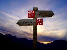 Madera señal indicando la dirección Oeste y este sobre cielo de Sierra Mágina