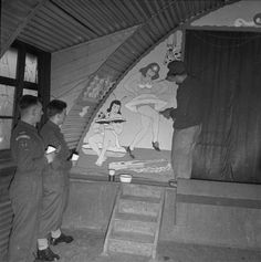 A German prisoner of war decorates the wall of a NAAFI hut in a British Army camp near Brussels.