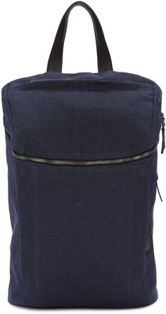 Linen backpack in 'blue black' navy. Leather carry handle at top. Adjustable leather shoulder straps with pin-buckle fastening. Zippered pocket at face. Zippered pocket at top. Zip closure at main compartment. Alternate zippered openings at face and side. Logo-embossed leather card slot and patch pocket at bag interior. Coated interior in black. Gunmetal-tone hardware. Tonal stitching. Approx. 11
