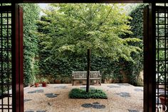 Surrounded by walls blanketed with star jasmine, a lime tree shades the pebbled sunken courtyard.