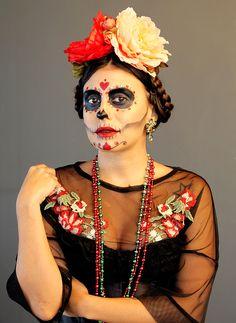 Carol Burgo veste fantasia de Catrina, com tiara de flores no estilo Frida Kahlo, vestido de tule com bordado floral e corpete de renda preto. Maquiagem artística de calavera mexicana, com aplicação de brilhos, para Carnaval de rua,  Halloween ou Dia de Los Muertos.