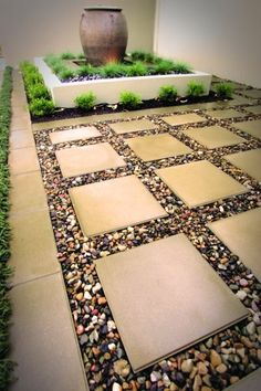Coloured pebbles are used to great effect in between large format pavers. Do this to extend the tiny patio area into the grassy lawn front and back-less mud and more stable area for container gardening.