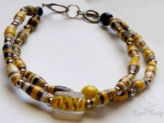 A bio-hazard, a crime scene, a #zombie infestation ...#yellow and #black are the colors of #caution and this #handmade one of a kind, #paper bead bracelet features it beautifully.The glass bead in the middle reminds me of a #DNA strand, or perhaps a rage #virus that must be handled with caution.#ooak
