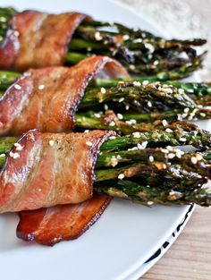 Marinate asparagus in Italian dressing for 1.5 hrs then wrap them in bacon and sprinkle on sesame seeds. Bake at 400 for 35 minutes.