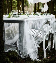 Table avec plateau blanc et fin voilage LILL en guise de nappe, avec chaises pliantes blanches.