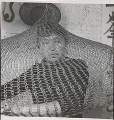 Untitled (Ruth Asawa on bed looking out of looped-wire sculpture) by Imogen Cunningham