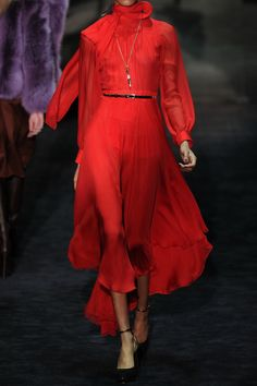 Gucci's striking silk-chiffon gown reignites our passion for opulent '70s-inspired glamour this fall. Take your style cue from the runway and offset the vibrant flame red hue with gold jewelry and sky-scraping heels.    Shown here with: Philippe Audibert anklet - worn as bracelet, Kenneth Jay Lane bracelet, Roberto Cavalli ring, Gucci belt, Christian Louboutin boots, Emilio Pucci clutch.