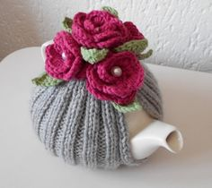 "GORGEOUS TEA COSY - Handmade Silver Grey with 5 Pink Flowers with Pearl button centers. **READY TO SHIP** This tea cosy has been hand knitted in 100% acrylic yarn in a stretch rib pattern to fit your teapot snugly. Topped with 5 gorgeous cerise/ pink crochet flowers with white pearl button centers and pale green leaves. Each cosy is individually handmade by me in a smoke free environment. Measurements: Fits a 4/6 cup tea pot. Approximate size 7""/18cm high. Hand wash with car..."