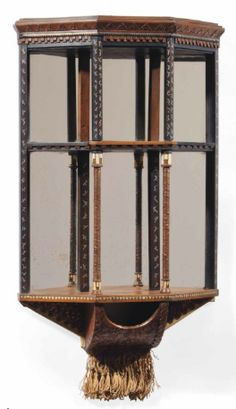 CARLO BUGATTI WALNUT, COPPER, VELLUM, PEWTER AND BONE HANGING AND MIRRORED GLASS WALL UNIT,  CIRCA 1900, Mirror backed and with shelves, united by copper wrapped and pewter inlaid supports, copper clad small enclosure with tassels below, 28 ½ in. (72.5 cm.) high; 17 ½ in. (44.5 cm.) wide; 5 ¼ in. (13.3 cm.) deep  |  SOLD $5,860 Christie's London, June 11, 2014