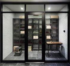 Basement boasts glass wine cellar filled with floor to ceiling white subway tiles with dark grout framing metal wine shelving alongside black stool and vintage wood and iron table atop dark gray tiled floor.