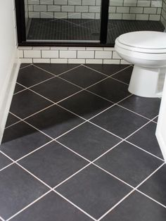 The terrace suite bathroom floor features 12x12 black ceramic tiles laid in a diagonal pattern and grouted in a light hue for contrast.