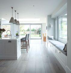 grande cuisine moderne et ouverte aménagée avec un îlot avec espace repas et une banquette sous fenêtre avec rangements