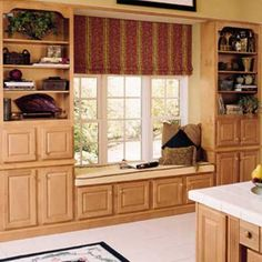 Ingredients for an inexpensive built-in window seat and storage: six standard kitchen wall cabinets, two 48-inch-tall bookcase units, trimmed with decorative crown molding and two 15-inch-tall, over-the-refrigerator cabinets set side-by-side. | Photo: Thomas-Rouchard Studios | thisoldhouse.com